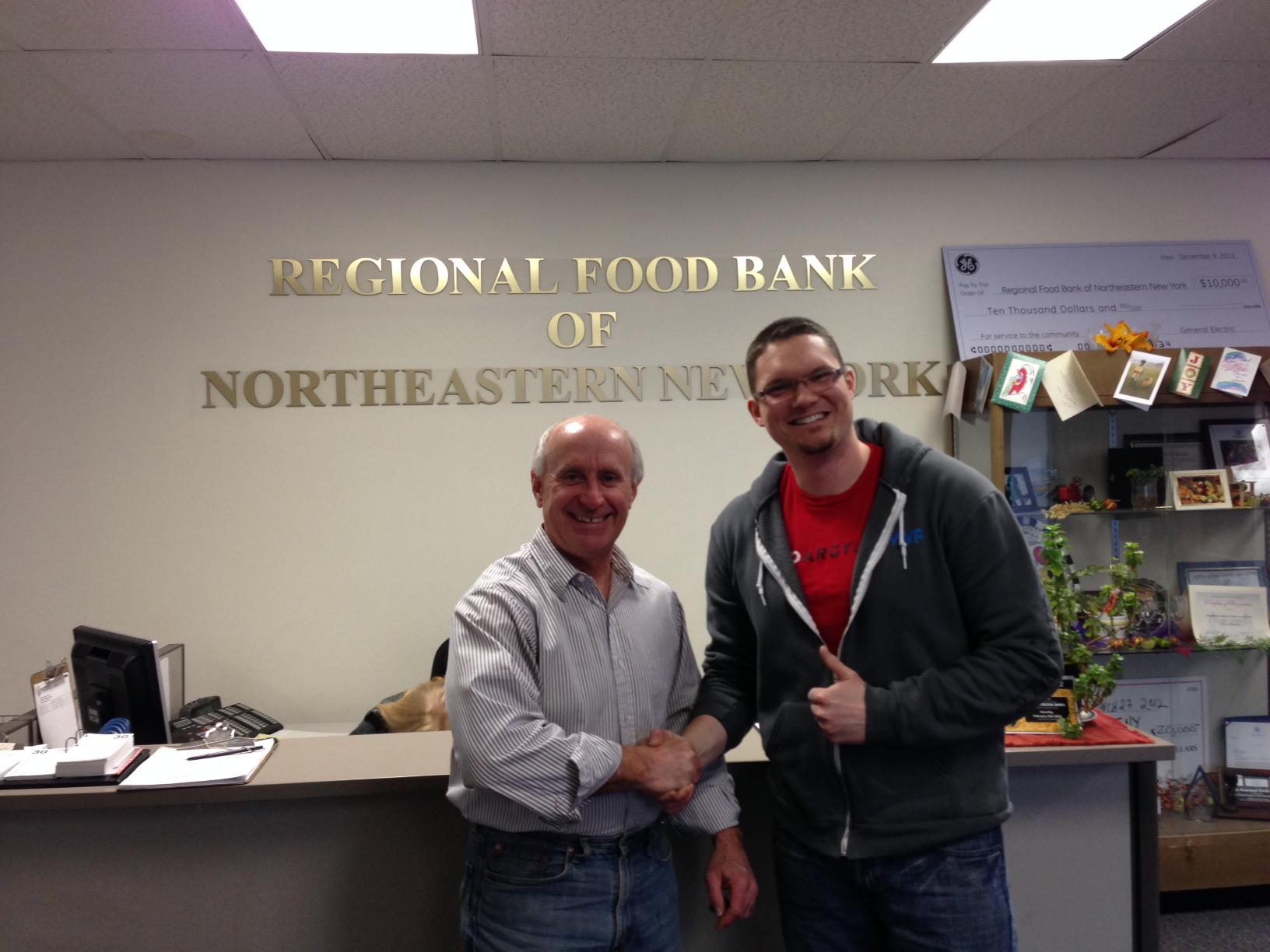 Garry and Mark Quandt shaking hands after the 2013 donation